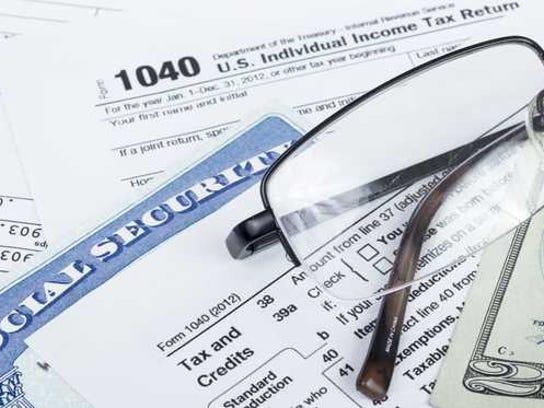A W2, 1040 form, social security card, twenty dollar bill, and reading glasses.