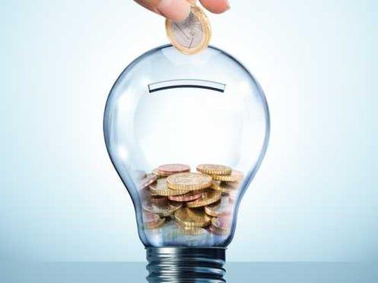 A hand puts coins into a clear bank shaped like a lightbulb.