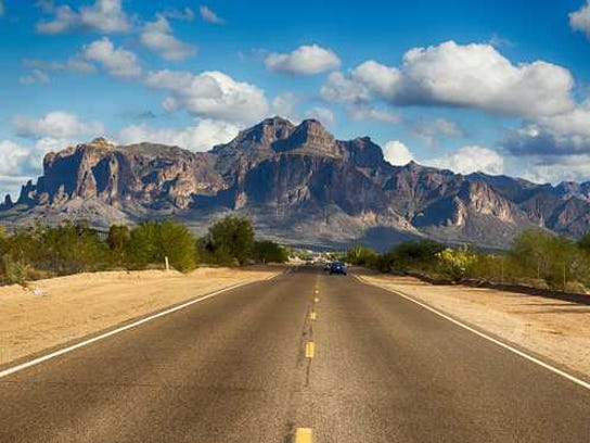 The open road with blue sky and mountains.