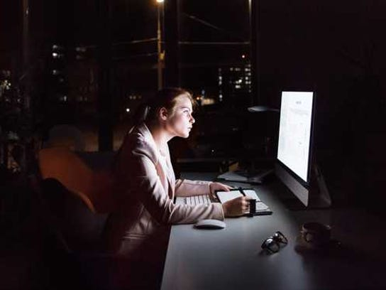 woman sitting in front of computer in dark office at