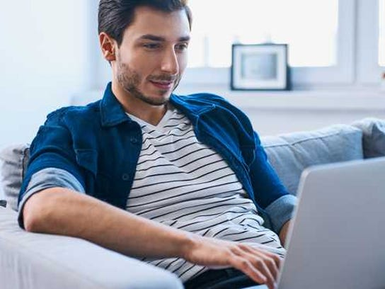 A man sits on a couch with a laptop in front of him.