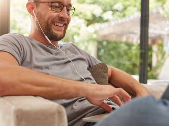 A man wearing headphones is sitting on a couch with