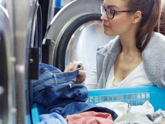 Woman removes laundry from a washing machine.