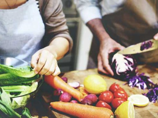 Two people in aprons prepping fresh ingredients to