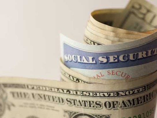 A Social security card rolled up in a wad of paper money.
