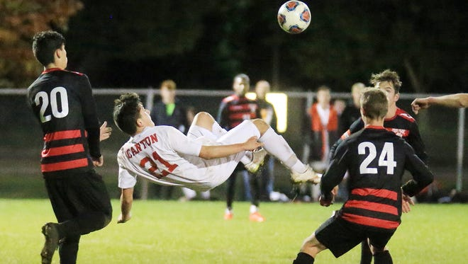 Canton's Alex Spratte goes airborne to kick the ball Thursday night while Grand Blanc's Anthony Gasso (left) and Brennan Kane (No. 24) converge.