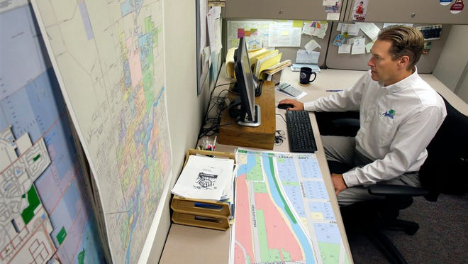 Dan Steenbock, a city of Appleton property assessor, works on land value revues at City Hall recently in downtown Appleton.