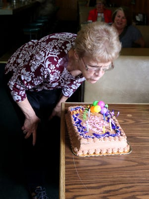 Marlene Blanchard, owner of the Court Street Dairy Lunch, blows out candles on a cake celebrating her birthday Tuesday.
