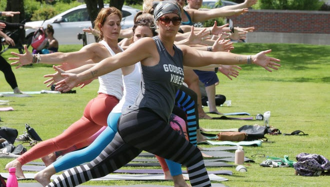 Yoga enthusiasts hold a pose during an International Yoga Day group session last week on the lawn of The American Club in Kohler.