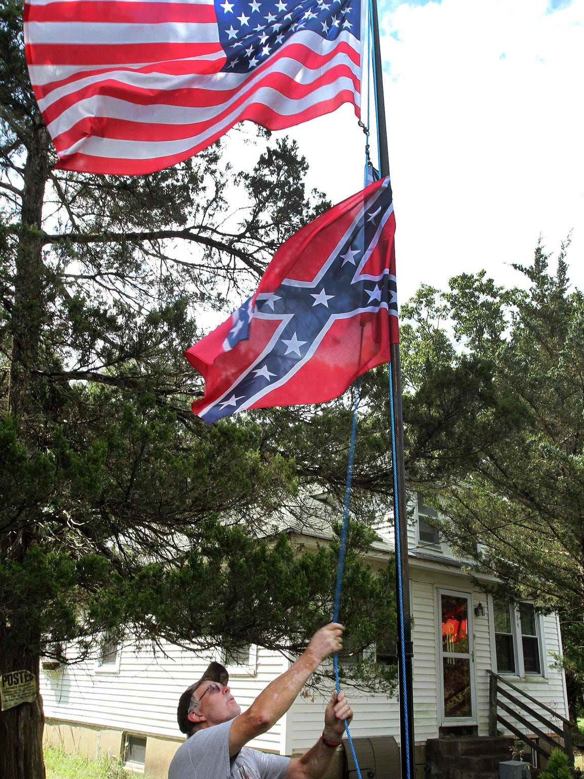 """Al Wright straightens the flags outside his home on Cedar Swamp Road in Jackson Township. The decades-long resident, who is weary of the changes in Jackson, believes the Confederate flag serves as a reminder that """"fathers and brothers"""" died flying it during the Civil War."""