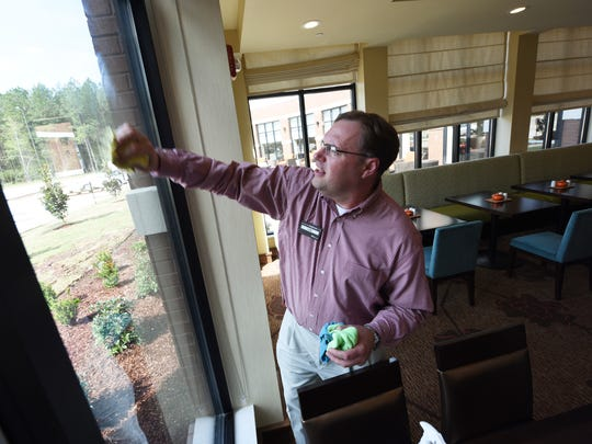 General manager Shawn Cochran helps tidy up the lobby of Flowood's new Hilton Garden Inn. The hotel opened this month near Longhorn Steakhouse off Lakeland Drive.