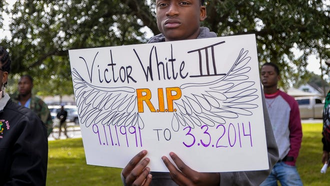 Eric Green Jr. holds a sign during a rally for Victor White III at the Iberia Parish Courthouse in New Iberia Saturday. Victor White III allegedly committed suicide while in custody of the Iberia Parish Sheriff's deputies in 2014 with the family calling for answers from the police.