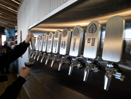 Beertender Paige Hanson fills a glass of beer for a