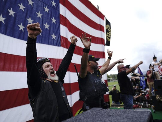 "FILE - In this Sept. 26, 2020 file photo, members of the Proud Boys, including leader Enrique Tarrio, second from left, gesture and cheer on stage as they and other right-wing demonstrators rally in Portland, Ore. President Donald Trump didn't condemn white supremacist groups and their role in violence in some American cities this summer. Instead, he said the violence is a ""left-wing"" problem and he told one far-right extremist group to ""stand back and stand by."" His comments Tuesday night were in response to debate moderator Chris Wallace asking if he would condemn white supremacists and militia groups. Trump's exchange with Democrat Joe Biden left the extremist group Proud Boys celebrating what some of its members saw as tacit approval."
