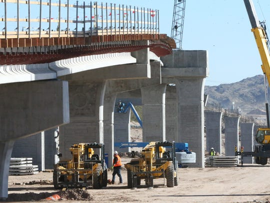 A construction crew works Monday on an on-ramp under