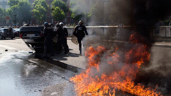 Riot police in Paris stand near a car set on fire during demonstrations against Uber on June 25, 2015.