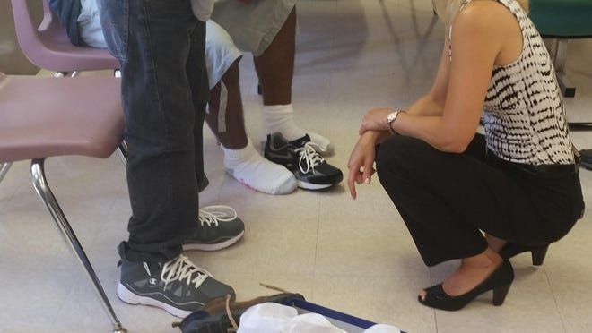 Dr. Jodie Sengstock of the MPMA fits a young man with a new pair of shoes.