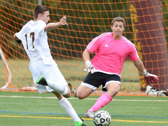 Arlington's Dillon Petrillo takes a shot on Roy C. Ketcham's goalie, Christopher Argiento during Wednesday's game at Arlington High School.  Though Petrillo scored earlier in the game, Argiento made the save on this shot.