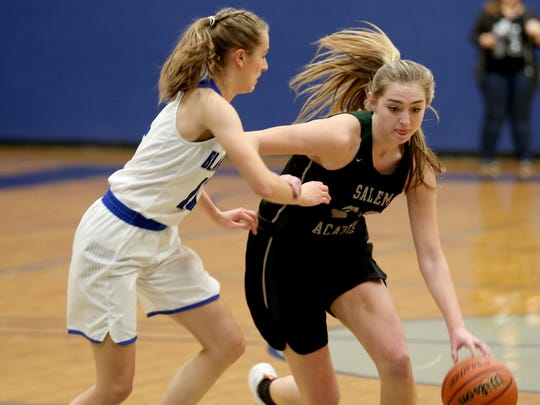 Salem Academy's Sydney Brown (24) drives past Blanchet's Trinity Phipps (11) in the first half of the Salem Academy vs. Blanchet girls basketball game at Blanchet Catholic School in Salem on Wednesday, Jan. 3, 2018. Salem Academy won the game 50-24.