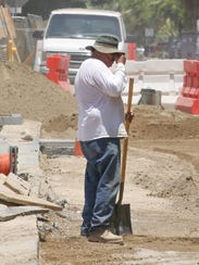 A construction worker wipes his brow while working