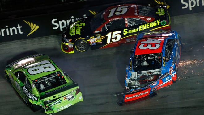 Kyle Busch (18), Clint Bowyer (15) and Aric Almirola (43) collide during a multicar wreck at Saturday's Irwin Tools Night Race.