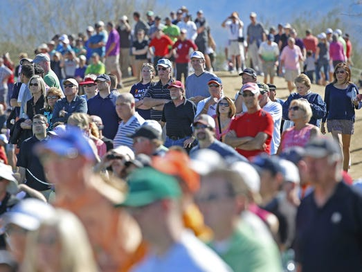 Fans crowd the fairways of the third hole during the