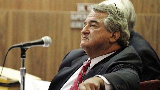 Pat Cooper listens to testimony in his 2014 termination hearing.