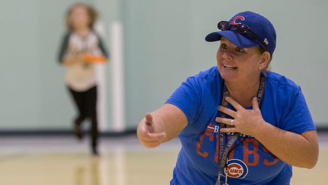 Michele Baumgartner, a physical education teacher, shows fourth graders how to properly throw a frisbee during gym class at Resurrection School Friday afternoon. Baumgartner has been teaching at Resurrection for 21 years and has been teaching physical education for seven of those years.