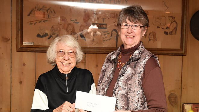 Opal House (left), owner of The Back Forty, presents $1,000 to Linda Masters, Christmas Wish Board president, for the Wish bike fund. The donation was the proceeds of the establishment's recent beef-stew fundraiser.