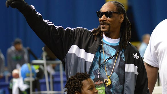Recording artist Snoop Dog waves to fans during the 2015 Under Armour All-America Game at Tropicana Field in January.