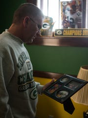 Mike Bogan, of Neenah, pauses to look at photos of