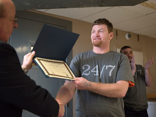 Inside/Out Dad graduate Michael Arnold accepts his certificate of achievement from re-entry coordinator Tim Carothers on Thursday, March 1, 2018, during a graduation ceremony at Madison County Penal Farm in Jackson.