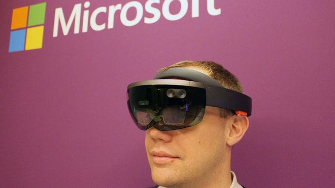 HoloLens director of communications Craig Cincotta wears the Microsoft altered reality headgear in a demonstration room at the Consumer Electronics Show on January 5, 2017 in Las Vegas. A group of Microsoft workers is demanding the company cancel a contract supplying the U.S. Army with HoloLens headsets that they say would turn real-world battlefields into a video game.