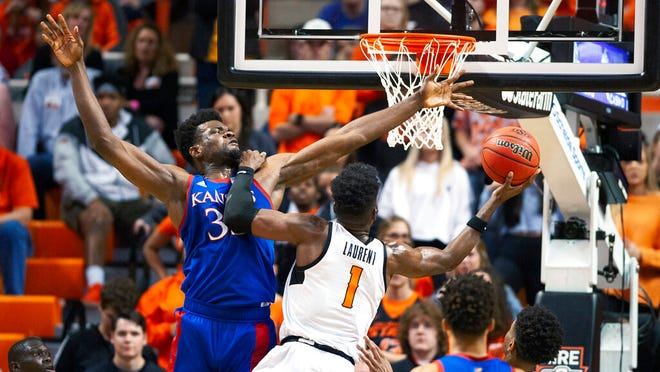 Oklahoma State guard Jonathan Laurent (1) leans on Kansas center Udoka Azubuike (35) while taking a shot during the second half of an NCAA college basketball game in Stillwater, Okla., Monday, Jan. 27, 2020. Kansas defeated Oklahoma State 65-50.