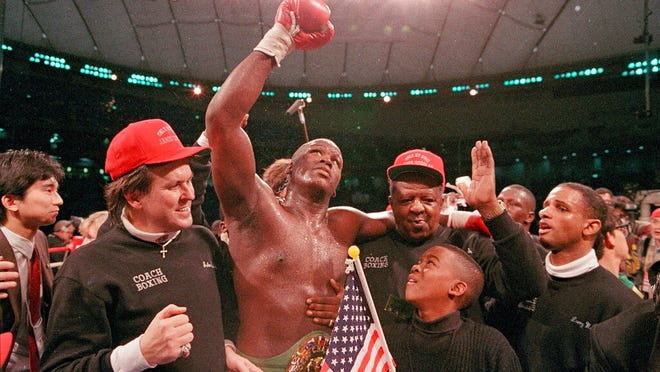 """From Feb. 11, 1990, heavyweight boxer James """"Buster"""" Douglas waves his gloved hand to the cheering crowd as he makes his way to the dressing room following a 10th round knockout victory over Mike Tyson in a scheduled 12-round championship bout at the Tokyo Dome.  In one of the more spectacular upsets in sports history, Douglas defeated Tyson, the reigning world heavyweight champion on Feb. 11, 1990, in Tokyo."""