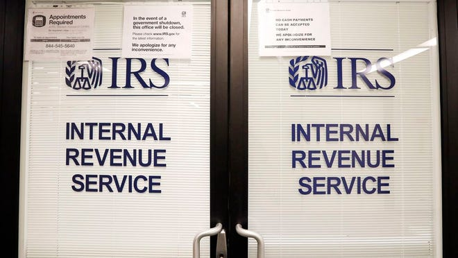 FILE - In this Jan. 16, 2019, file photo, doors at the Internal Revenue Service (IRS) in the Henry M. Jackson Federal Building are locked and covered with blinds as a sign posted advises that the office will be closed during the partial government shutdown in Seattle. Videos and reports claiming that you'll have to pay back the relief checks the federal government is sending to millions of Americans are false, federal agencies confirmed to The Associated Press.