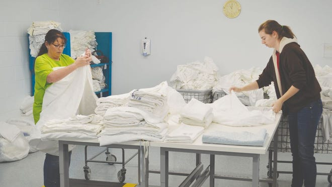 Pratt Regional Medical Center Laundry Supervisor Loretta Hitz, left, folds freshly-laundered sheets and other items at PRMC's in-house laundry facility, assisted by Laundry Specialist Nichole Moreland. PRMC purchased the laundromat at 820 West First Street late last year and began using it in January 2020. Savings are expected to amount to $100,000 annually from previous costs of out-sourcing the hospital's estimated 164,000-plus pounds of bedding and other items.