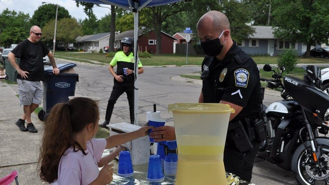 Lakeyn Warrick, 8, serves a cup of lemonade to Hilliard Division of Police officer Dustin Vance on Aug. 18 outside her Circle Drive residence in Hilliard. Lakeyn said she started the lemonade stand to raise money for the Central Ohio Canine Foundation.