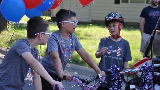 Sam Owsley (left), 8, his brother, Charlie Owsley, 10, and Anthony Whipp, 9, wait for the start of a Fourth of July parade on Norwich Street planned by residents in place of the canceled traditional parade. The Owsleys live on Norwich Street; Whipp also lives in Hilliard.