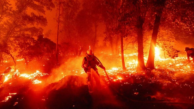 A firefighter battles the Creek Fire as it threatens homes in the Cascadel Woods neighborhood of Madera County, Calif., on Monday, Sept. 7, 2020.