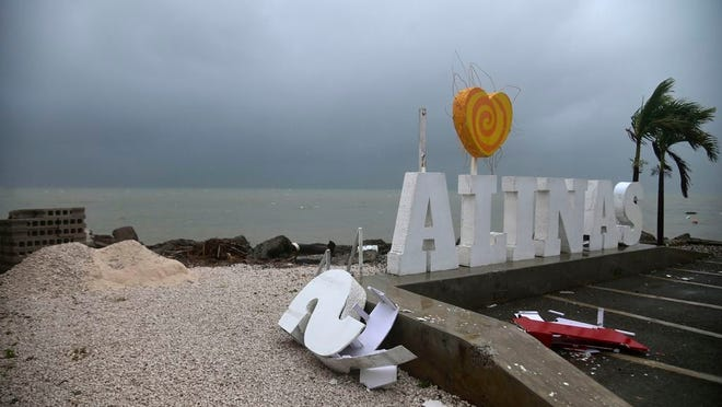 Remnants of a city sign lay on the beach damaged by Tropical Storm Laura in Salinas, Puerto Rico, Saturday, Aug. 22, 2020. Laura began flinging rain across Puerto Rico and the Virgin Islands on Saturday morning and was expected to drench the Dominican Republic, Haiti and parts of Cuba during the day on its westward course.