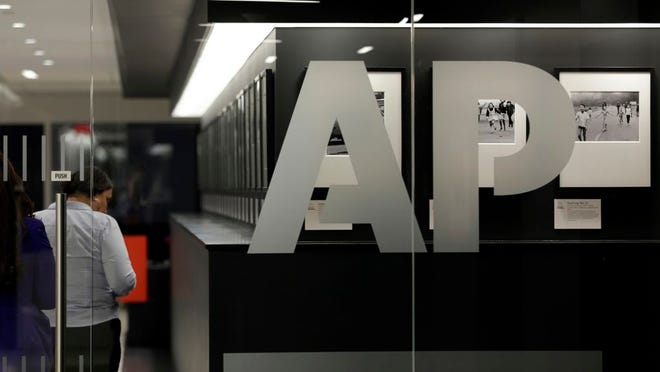 "AP Style-Capitalize Black Image ID : 20171837195876 FILE - In this April 18, 2017, file photo, people walk by Associated Press photographs on display at The AP headquarters in New York. The Associated Press changed its influential style guide Friday, June 19, 2020, to capitalize the ""b"" in the term Black when referring to people, weighing in on a hotly debated issue."