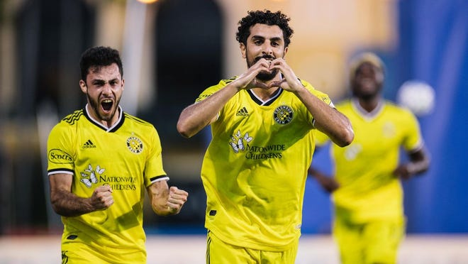 Columbus Crew midfielder Youness Mokhtar (front) and left back Milton Valenzuela (back) celebrate a first half goal in the Crew's 1-0 win over Atlanta United at the MLS is Back Tournament near Orlando, Florida.