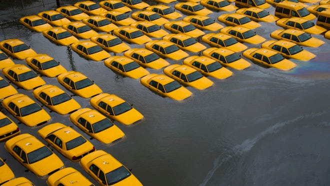 FILE - In this Tuesday, Oct. 30, 2012 file photo, a parking lot full of yellow cabs is flooded as a result of Superstorm Sandy in Hoboken, NJ.