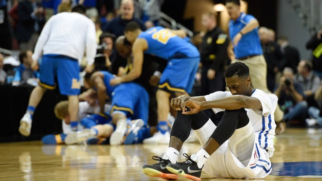 Southern Methodist Mustangs guard Ryan Manuel (1) sits Thursday as the UCLA Bruins celebrate their 60-59 win in the second round of the 2015 NCAA Tournament. The game was played at the KFC Yum! Center in Louisville, Ky.
