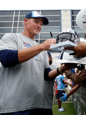 Tennessee Titans coach Ken Whisenhunt signs autographs following a 2014 training camp practice.