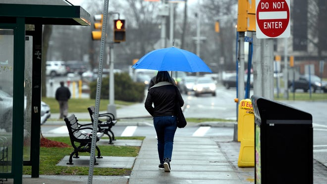 A woman walks down Main street in Hackensack on another rainy day in North Jersey on Tuesday, March 28, 2017.
