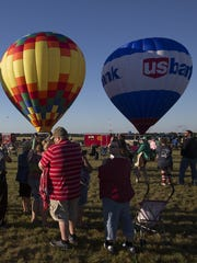 A crowd gathers to watch as balloons go up during the