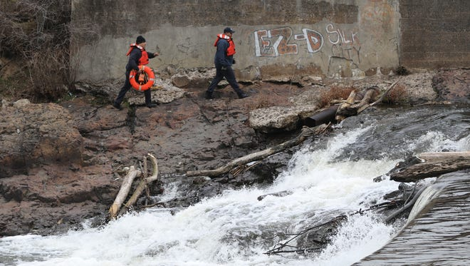 Emergency workers approach the area where a body was found after an apparent suicide. The body was recovered near the hydroelectric plant at the Great Falls in Paterson late Tuesday afternoon.