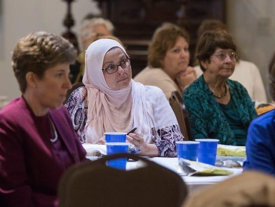 Salma Ashmani, center, and others listen as 2018 International